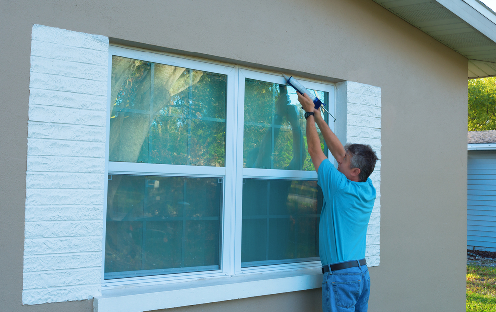 A man applying a storm window over his window.
