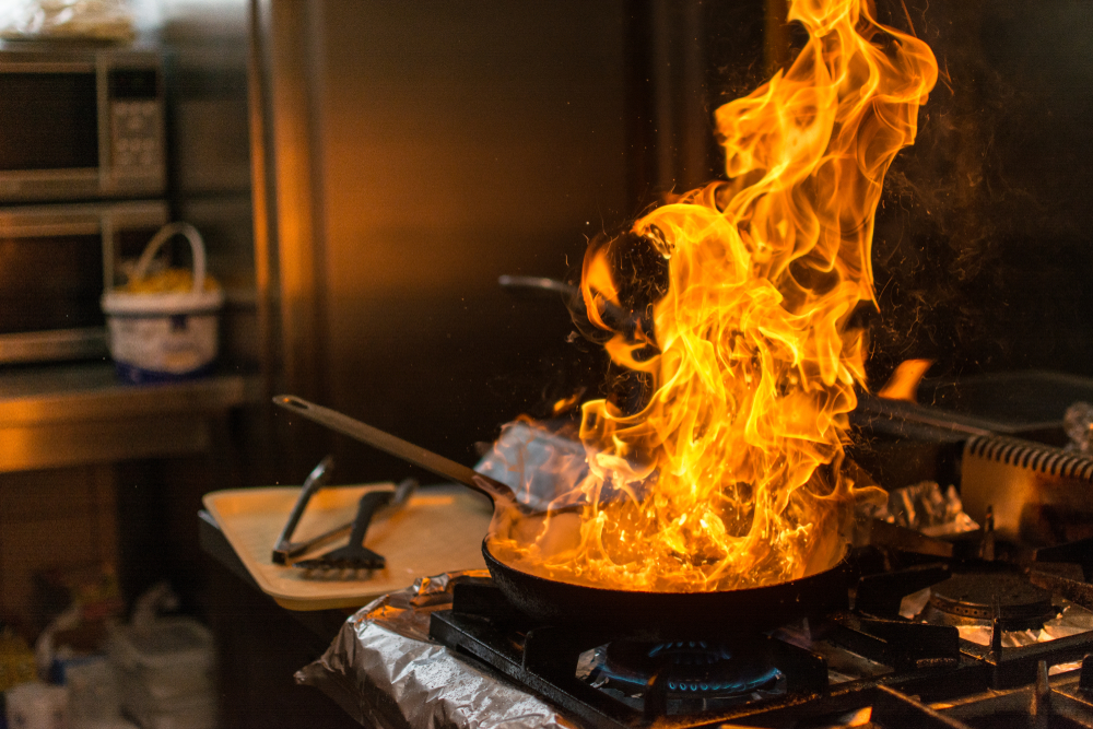 A pan in the kitchen that's on fire.