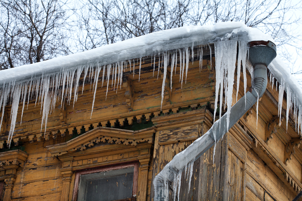 A home's roof with a frozen gutter and icicles.