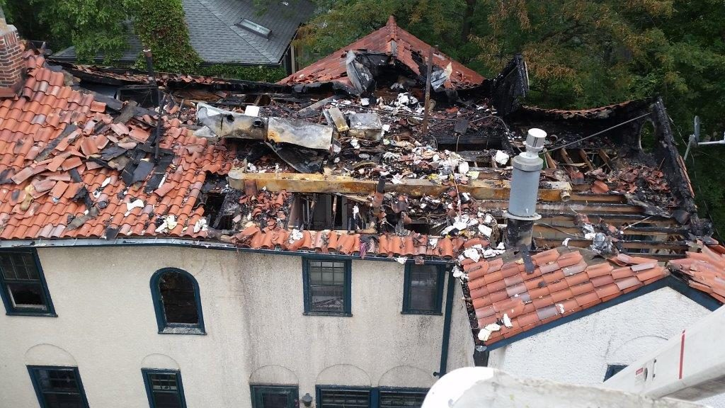 Massive damage to the roof of a home because of a fire.