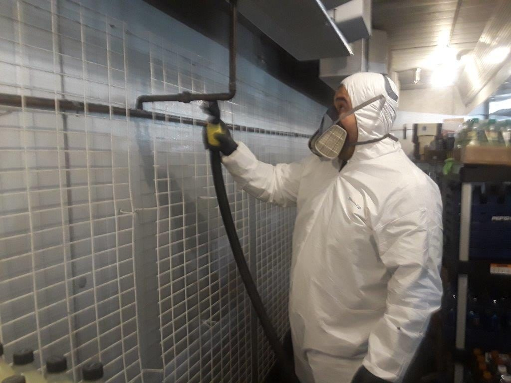 A Rapid Restoration tech cleaning up a mess in a bio suit.