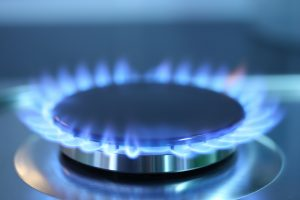 A lit gas burner on a stove.