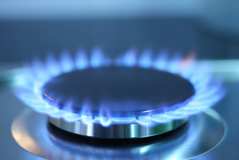 A lit gas burner on a stove.