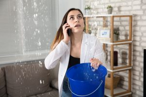A woman catching water in a bucket and calling a company.