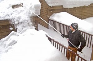 man using a snow rake to clear snow from his roof