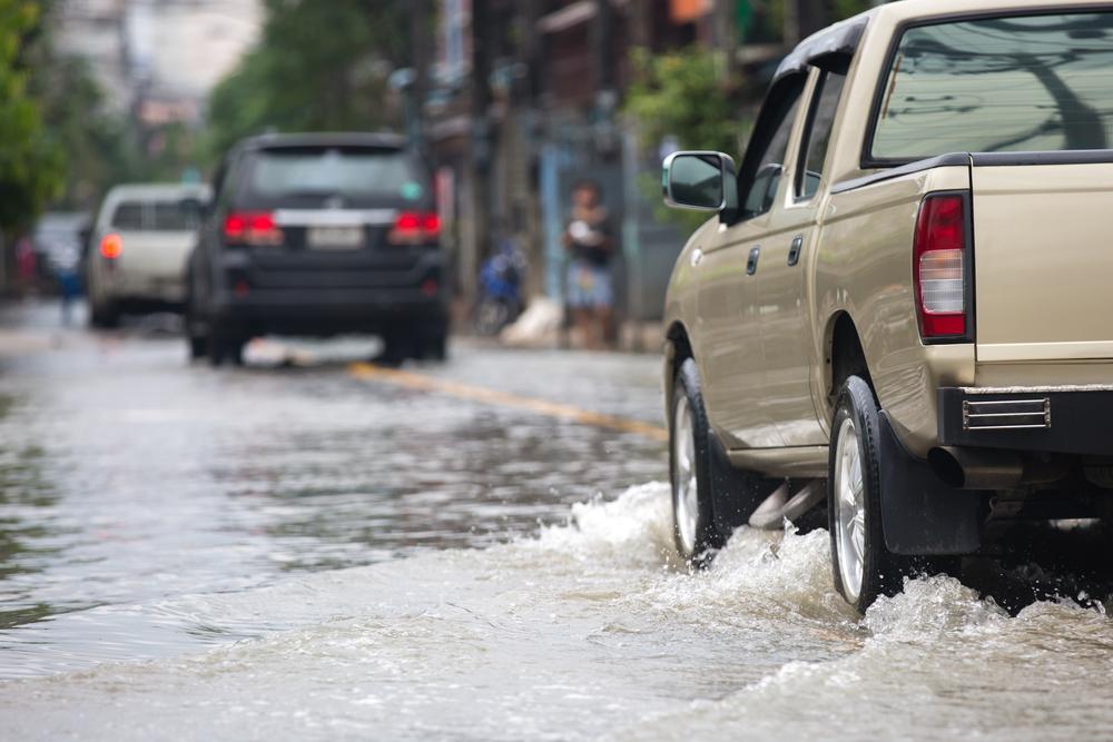 A pickup truck driving through deep water.