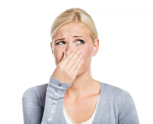 Woman holding her nose because it stinks