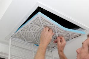 A man changing the air filter from a vent in the ceiling.