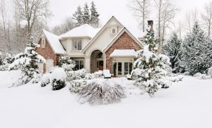 A home covered in snow and ice on a cloudy day.