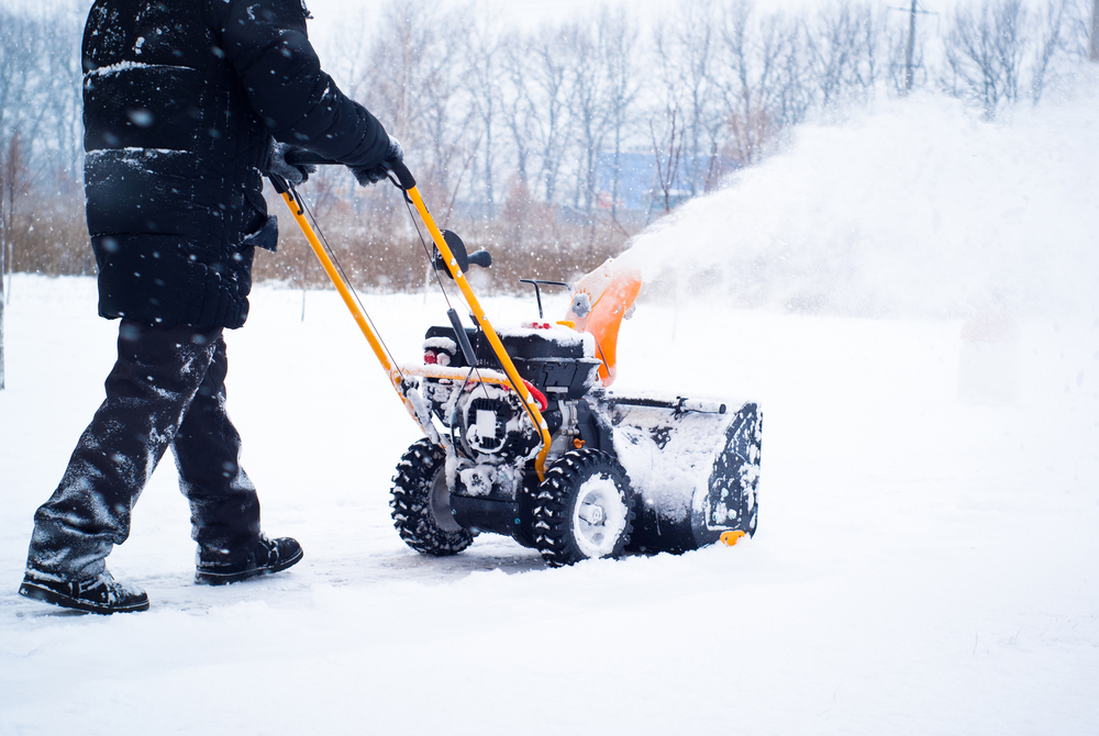 Man using a snowblower on his driveway