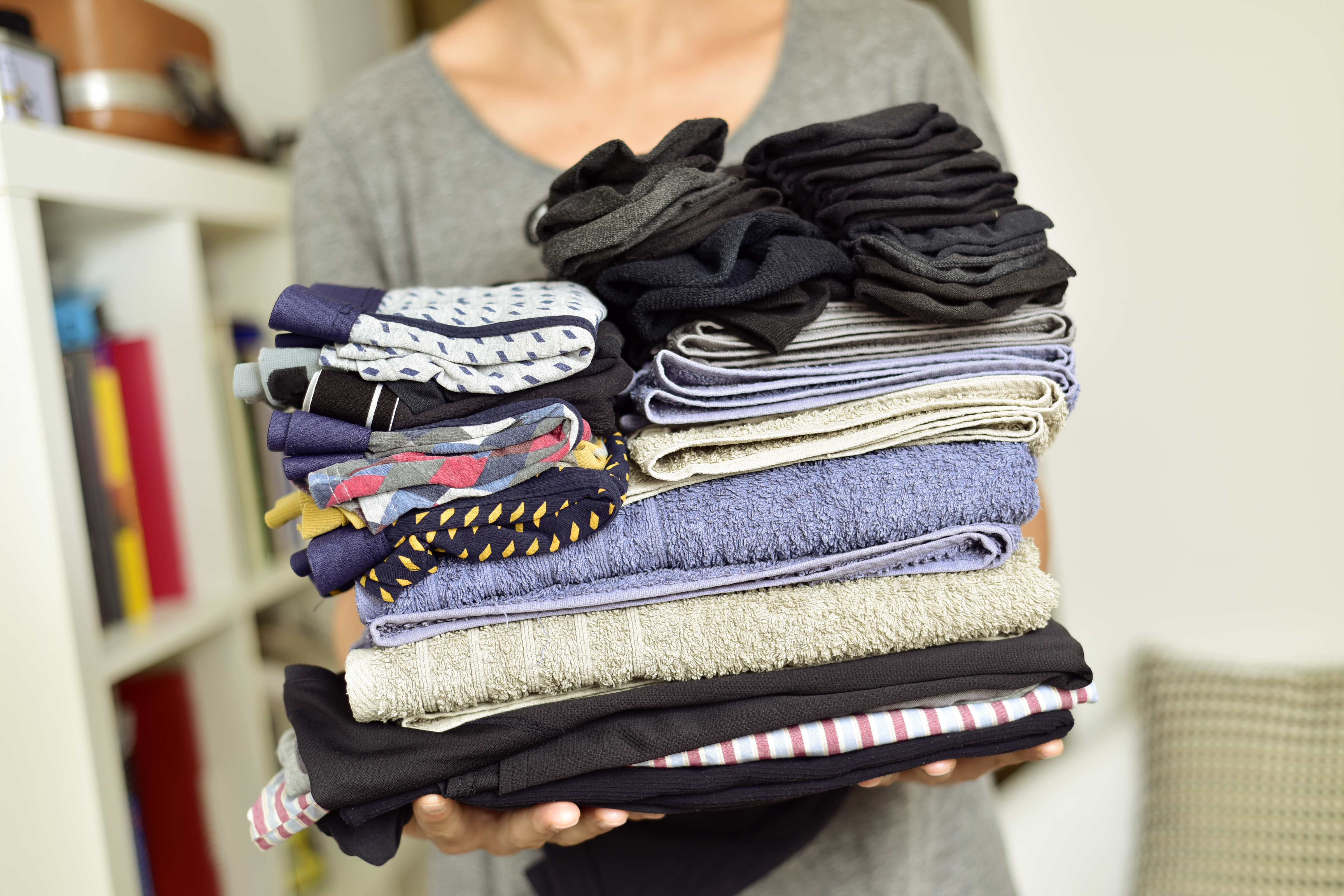 woman holding a bunch of folded clothes
