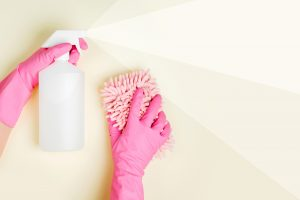 woman spraying cleaner with gloves and a scrubber in her hand